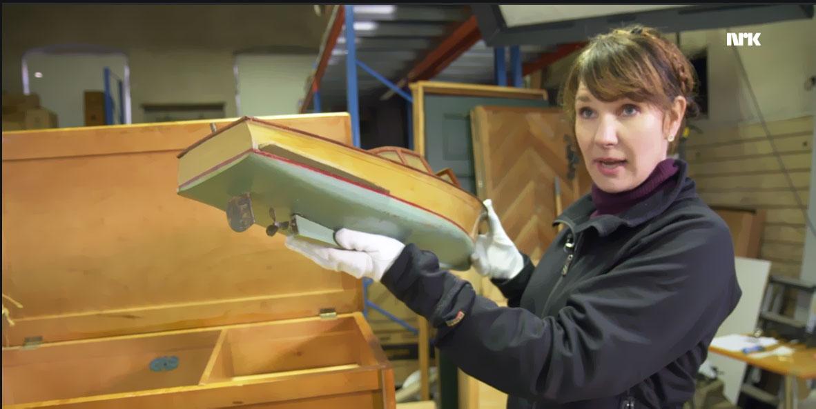 Marianne Hylbak, registrar ved De kongelige samlinger viser frem modellbåten i NRKs TV-program.